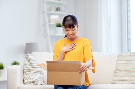 mensen, levering, handel, scheepvaart en shopping concept - gelukkig Aziatische jonge vrouw met kartonnen pakje doos thuis