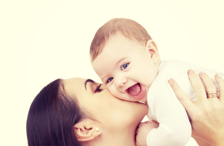 baby with mama: family and happy people concept - mother kissing her baby Stock Photo