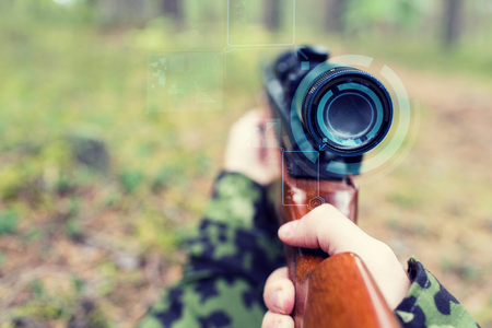 infantryman: hunting, war, army, technology and people concept - close up of young soldier or sniper hands holding gun with virtual screen projection and aiming in forest Stock Photo