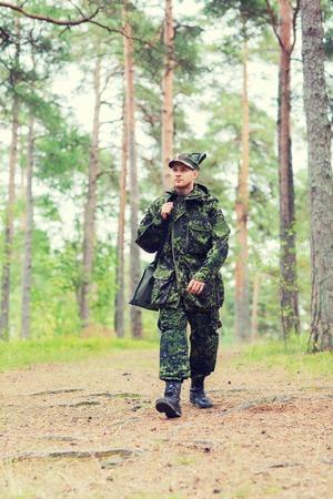 Jagd, Krieg, Armee und Volk Konzept - junger Soldat, Förster oder Jäger mit Gewehr im Wald spazieren