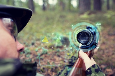 weapon: hunting, war, army, technology and people concept - close up of young soldier or sniper holding gun with virtual screen projection and aiming in forest