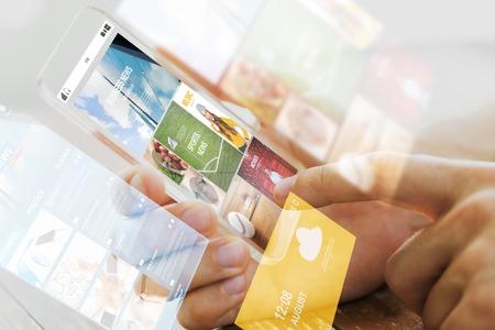 ビジネス、技術、マスメディア、人々 の概念 - は、画面上インターネット ニュースの web ページを持つ透明なスマート フォンを持っている男性の手