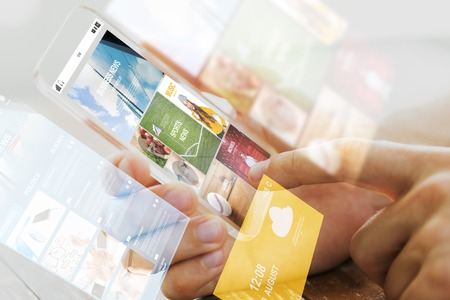 business, technology, mass media and people concept - close up of male hand holding transparent smartphone with internet news web page on screen Foto de archivo
