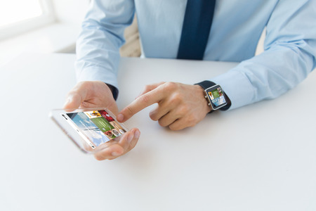 web screen: business, technology, media and people concept - close up of male hand holding and showing transparent smart phone and watch at office with web applications on screen