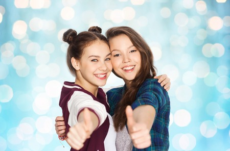 amigos abrazandose: people, friends, teens and friendship concept - happy smiling pretty teenage girls hugging and showing thumbs up over blue holidays lights background