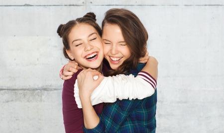 amigos abrazandose: las personas, las emociones, los adolescentes y el concepto de la amistad - sonriendo feliz Adolescentes bonitos abrazando y riendo sobre fondo gris de la pared de hormig�n