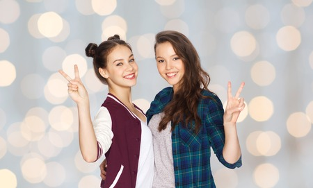 amigos abrazandose: people, friends, teens and friendship concept - happy smiling pretty teenage girls hugging and showing peace hand sign over holidays lights background