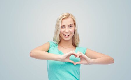 sweet smile: gesture and people concept - smiling young woman or teenage girl showing heart shape made of fingers over gray background