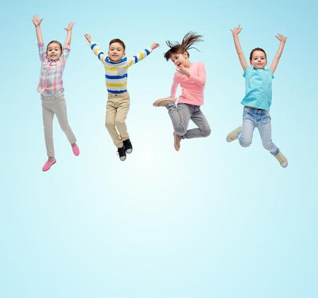 niños felices: la felicidad, la infancia, la libertad, el movimiento y el concepto de la gente - los pequeños niños felices que saltan en el aire sobre fondo azul