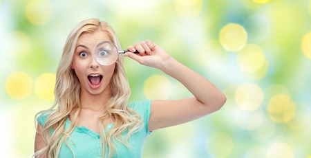 glass background: vision, exploration, investigation, education and people concept - happy smiling young woman or teenage girl looking through magnifying glass over summer green lights background