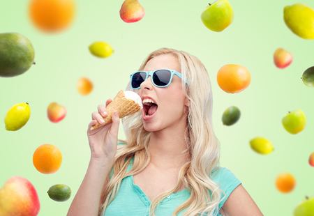 over eating: summer, junk food and people concept - young woman or teenage girl in sunglasses eating ice cream over green natural background with fruits