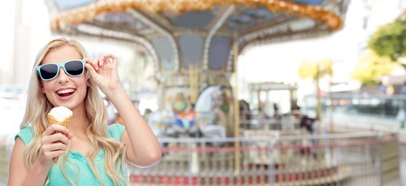 turnabout: summer, junk food and people concept - young woman or teenage girl in sunglasses eating ice cream over carousel at amusement park background