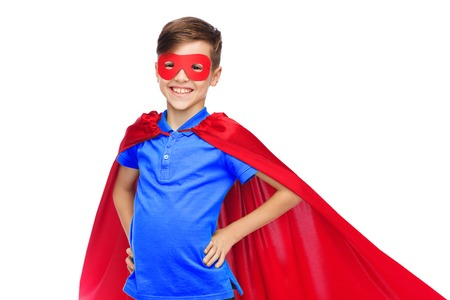 latin child: childhood, carnival costume and people concept - happy boy in red superhero cape and mask