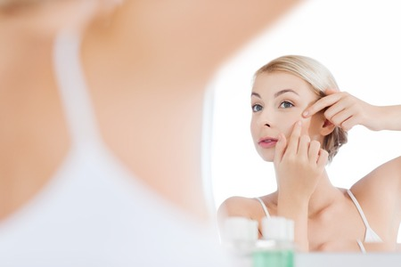 young woman face: beauty, hygiene, skin problem and people concept - young woman looking to mirror and squeezing pimple at home bathroom Stock Photo