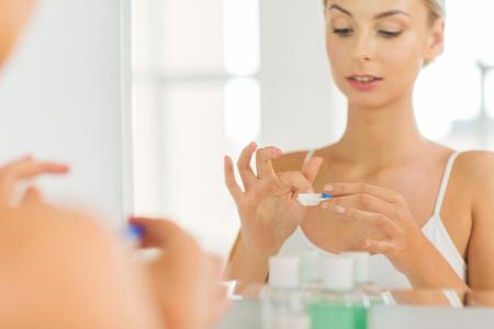 iletişim: güzellik, vizyon, görme, göz ve insanlar kavramı - yakın ev banyoda aynaya kontakt lens uygulanması genç kadının kadar Stok Fotoğraf