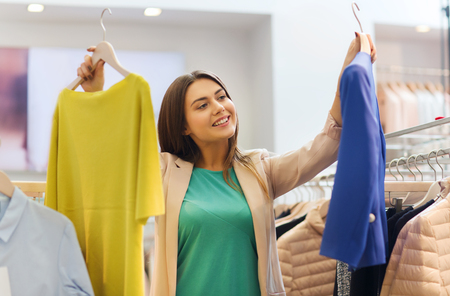 choosing: sale, clothes , shopping, fashion and people concept - happy young woman choosing between shirt and jacket at clothing store