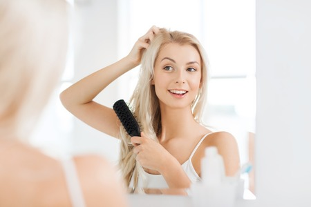 beauty, grooming and people concept - smiling young woman looking to mirror and brushing hair with comb at home bathroom Stock Photo