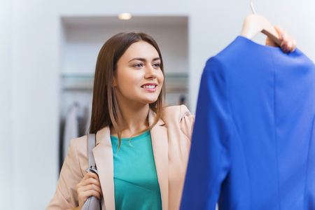 choosing clothes: sale, shopping, fashion, style and people concept - happy young woman choosing clothes in mall or clothing store Stock Photo