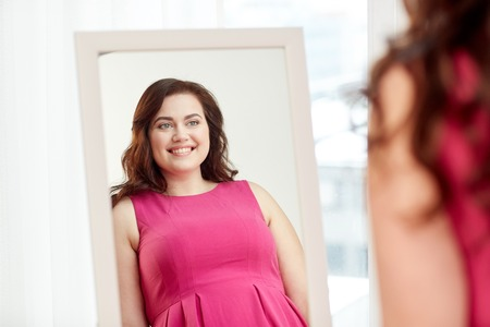 clothing, wardrobe, fashion, style and people concept - happy plus size woman posing at mirror at home Stockfoto