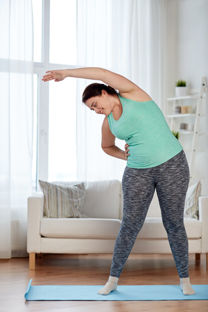 fitness, sport, exercising, training and lifestyle concept - smiling plus size woman stretching on mat at home Imagens