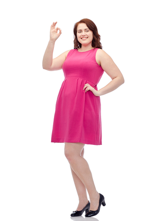 gesture, portrait and people concept - smiling happy young plus size woman posing in pink dress