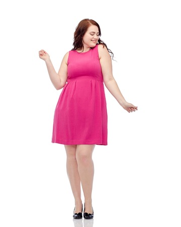 donna che balla: party and people concept - smiling happy young plus size woman posing in pink dress dancing Archivio Fotografico
