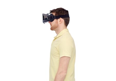 entertainment concept: 3d technology, virtual reality, entertainment and people concept - young man with virtual reality headset or 3d glasses