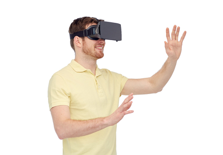 3d technology, virtual reality, entertainment and people concept - happy young man with virtual reality headset or 3d glasses playing game Stock Photo