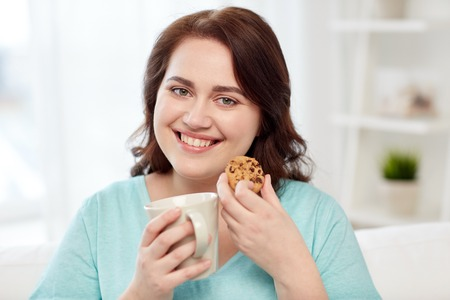 PRETTY WOMEN: people, junk food, unhealthy eating and leisure concept - happy plus size young woman with cup of tea with cookie at home Stock Photo