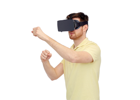 mediated: 3d technology, virtual reality, entertainment and people concept - young man with virtual reality headset or 3d glasses playing game and fighting