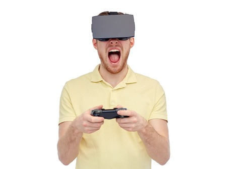 mediated: 3d technology, virtual reality, entertainment and people concept - young man with virtual reality headset or 3d glasses playing with game controller gamepad and screaming Stock Photo