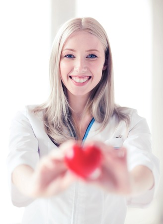 medical doctor: healthcare and medical concept - female doctor with heart