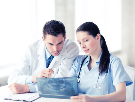 medical doctors: healthcare, medical and radiology concept - two doctors looking at x-ray