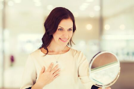 buyer: sale, consumerism, shopping and people concept - happy woman choosing and trying on pendant at jewelry store Stock Photo