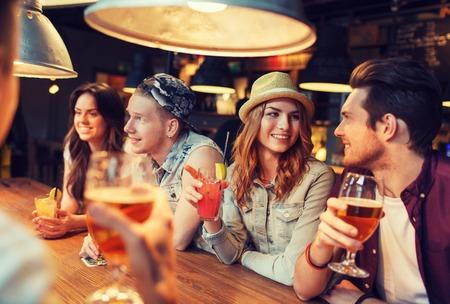 Personen, Freizeit, Freundschaft und Kommunikation Konzept - glücklich lächelnd Gruppe von Freunden trinken Bier und Cocktails im Gespräch an der Bar oder im Pub