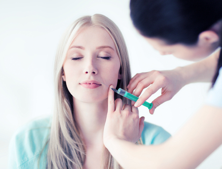 antiaging: beauty, healthcare and medical concept - beautician with patient doing anti-aging injection in hospital