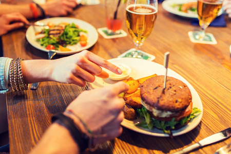people, leisure, friendship, eating and food concept - close up of friends hands with burger at bar or pub Stock Photo