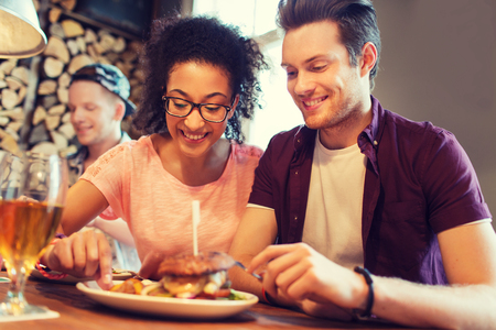 burgers: people, leisure, friendship, party and communication concept - group of happy smiling friends eating burger together at bar or pub