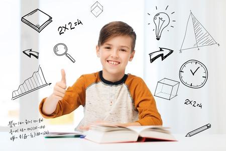 onderwijs, jeugd, mensen en school concept - gelukkige student jongen met boek en laptop blijkt thumbs up thuis via wiskundige krabbels Stockfoto