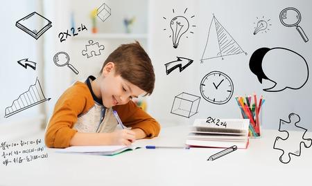 教育、子供のころ、人々、宿題、学校のコンセプト - 学生少年を浮かべて数学的な落書きを自宅のノートに書いて本 写真素材