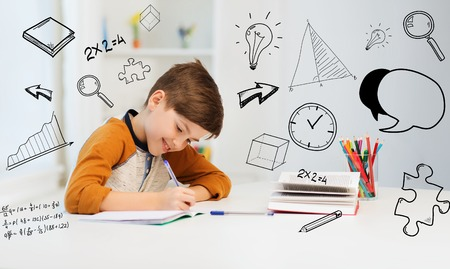 education, childhood, people, homework and school concept - smiling student boy with book writing to notebook at home over mathematical doodles Foto de archivo