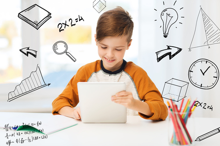 leisure, children, education, technology and people concept - smiling boy with tablet pc computer and notebook at home over mathematical doodles Stock Photo