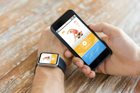 sport, fitness, technology, responsive design and people concept - close up of male hand holding smart phone and wearing watch with sports application on screen