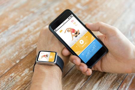 deporte, fitness, la tecnología, el diseño de respuesta y el concepto de la gente - cerca de la mano masculina que sostiene el teléfono inteligente y el uso de reloj con la aplicación deportiva en la pantalla