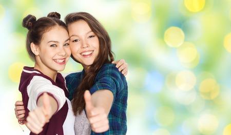 mensen, gebaar, zomer, tieners en vriendschap concept - gelukkig lachend mooie tienermeisjes knuffelen en tonen duimen omhoog over groene vakantie lichten achtergrond