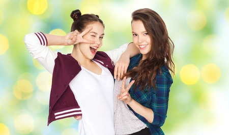 summer sign: people, friends, teens, summer and friendship concept - happy smiling pretty teenage girls showing peace hand sign over green holidays lights background Stock Photo