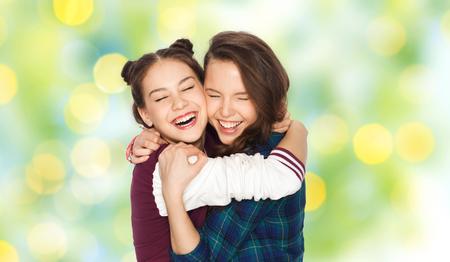 amigos abrazandose: las personas, las emociones, los adolescentes y el concepto de la amistad - sonriendo feliz Adolescentes bonitos que abrazan y que r�e sobre el fondo de las luces verdes de fiesta