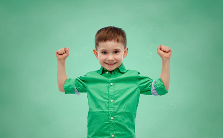 arms up: childhood, education, power, gesture and people concept - happy smiling little boy with raised hands showing his power over green school chalk board background