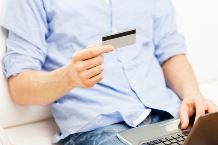 checking account: technology, people and online shopping concept - close up of man with laptop computer and credit card at home