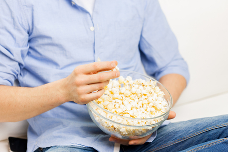 junkfood: food, junk-food, unhealthy eating and people concept - close up of man eating popcorn at home Stock Photo